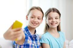 Muchachas felices con el smartphone que toma el selfie en casa Fotos de archivo