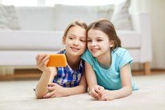 Muchachas felices con el smartphone que toma el selfie en casa Fotos de archivo libres de regalías