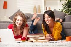Muchachas felices con la computadora portátil y los libros Imagen de archivo libre de regalías