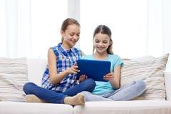 Muchachas felices con la PC de la tableta que se sienta en el sofá en casa Foto de archivo libre de regalías