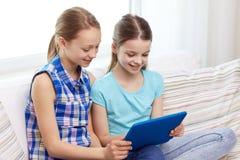 Muchachas felices con la PC de la tableta que se sienta en el sofá en casa Imagen de archivo