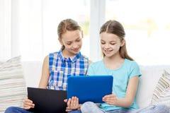 Muchachas felices con la PC de la tableta que se sienta en el sofá en casa Imágenes de archivo libres de regalías