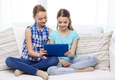 Muchachas felices con la PC de la tableta que se sienta en el sofá en casa Fotografía de archivo libre de regalías