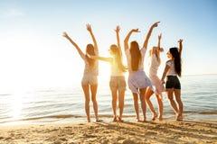 Muchachas felices con la playa aumentada de la puesta del sol de los brazos imágenes de archivo libres de regalías