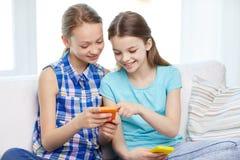 Muchachas felices con los smartphones que se sientan en el sofá Foto de archivo libre de regalías