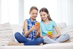 Muchachas felices con los smartphones que se sientan en el sofá Fotos de archivo libres de regalías