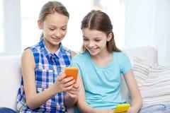 Muchachas felices con los smartphones que se sientan en el sofá Imágenes de archivo libres de regalías