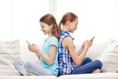Muchachas felices con los smartphones que se sientan en el sofá Imagen de archivo libre de regalías
