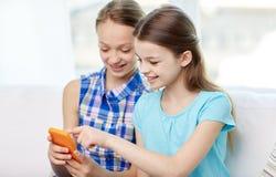 Muchachas felices con los smartphones que se sientan en el sofá Fotografía de archivo libre de regalías