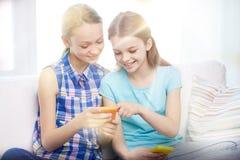 Muchachas felices con los smartphones que se sientan en el sofá Fotografía de archivo