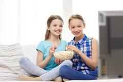 Muchachas felices con palomitas que ven la TV en casa Imágenes de archivo libres de regalías