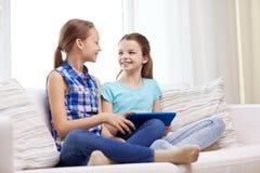 Muchachas felices con PC de la tableta que hablan en casa Imagen de archivo