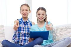 Muchachas felices con PC de la tableta y el mostrar los pulgares para arriba Fotos de archivo