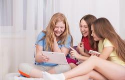 Muchachas felices con PC del smartphone y de la tableta Fotos de archivo