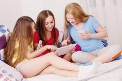 Muchachas felices con PC del smartphone y de la tableta en casa Imagenes de archivo