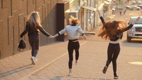 Muchachas felices de los amigos femeninos alegres que funcionan con la calle almacen de metraje de vídeo