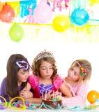 Muchachas felices de los niños que soplan la torta de la fiesta de cumpleaños fotografía de archivo