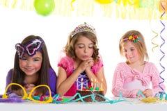 Muchachas felices de los niños que soplan la torta de la fiesta de cumpleaños Imagenes de archivo