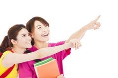 Muchachas felices del estudiante que sostienen los libros y que señalan en alguna parte Imagen de archivo libre de regalías