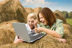 Muchachas felices del país que se relajan con la computadora portátil Foto de archivo libre de regalías