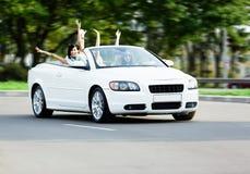 Muchachas felices en el cabriolé con los brazos extendidos Foto de archivo