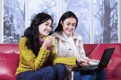 Muchachas felices en ropa caliente usando el ordenador portátil Foto de archivo