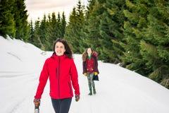Muchachas felices en un viaje que camina en la montaña nevosa Fotografía de archivo libre de regalías