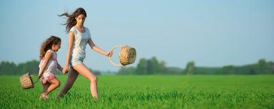 Muchachas felices jovenes que corren cestas de la bruja en el campo de trigo verde Imagen de archivo libre de regalías