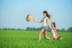 Muchachas felices jovenes que corren cestas de la bruja en el campo de trigo verde Foto de archivo