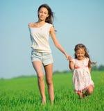 Muchachas felices jovenes que corren en el campo de trigo verde Fotos de archivo libres de regalías