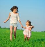 Muchachas felices jovenes que corren en el campo de trigo verde Imagen de archivo