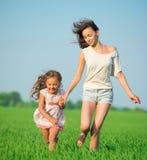 Muchachas felices jovenes que corren en el campo de trigo verde Imágenes de archivo libres de regalías