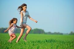 Muchachas felices jovenes que corren en el campo de trigo verde Imagenes de archivo