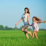 Muchachas felices jovenes que corren en el campo de trigo verde Imagen de archivo libre de regalías