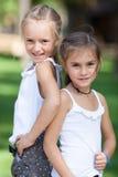 Muchachas felices maravillosas que se colocan en el césped Fotografía de archivo