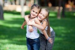 Muchachas felices maravillosas que se colocan en el césped Imagen de archivo