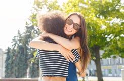 Muchachas felices que abrazan mientras que camina en la ciudad foto de archivo