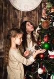 Muchachas felices que adornan el árbol de navidad Imágenes de archivo libres de regalías