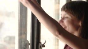 Muchachas felices que agitan a través de ventana almacen de video