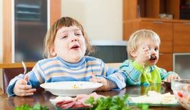 Muchachas felices que comen la comida de las placas Imágenes de archivo libres de regalías