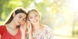 Muchachas felices que escuchan los auriculares en Autumn Day maravilloso Fotos de archivo libres de regalías