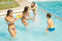 Muchachas felices que juegan con el niño en piscina con el arma de agua que salpica el agua Imagen de archivo libre de regalías