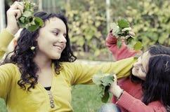 Muchachas felices que juegan con las hojas en jardín Fotos de archivo libres de regalías