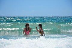 Muchachas felices que juegan en el océano hermoso Imagen de archivo