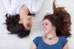 Muchachas felices que ponen en el suelo Imagen de archivo libre de regalías
