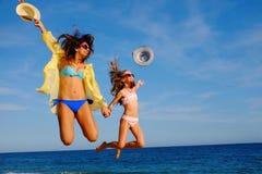 Muchachas felices que saltan junto en la playa Imagenes de archivo