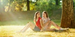 Muchachas felices que se sientan con los teléfonos de Mobil en el prado del verano Imagen de archivo libre de regalías