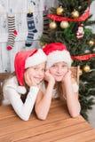 Muchachas felices que se sientan en la tabla y para la celebración del Año Nuevo que espera y de la Navidad Imágenes de archivo libres de regalías