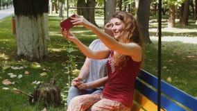 Muchachas felices que toman el selfie con el smartphone en un banco en el parque almacen de video