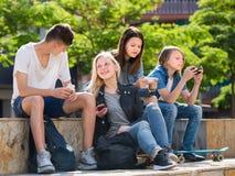 Muchachas felices y muchachos que juegan con los teléfonos móviles Fotos de archivo libres de regalías